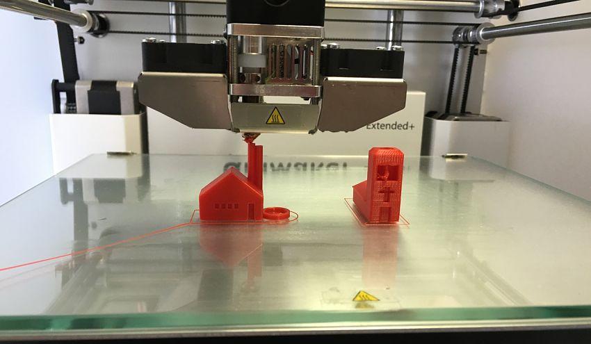 3D printer prints 2 miniature buildings