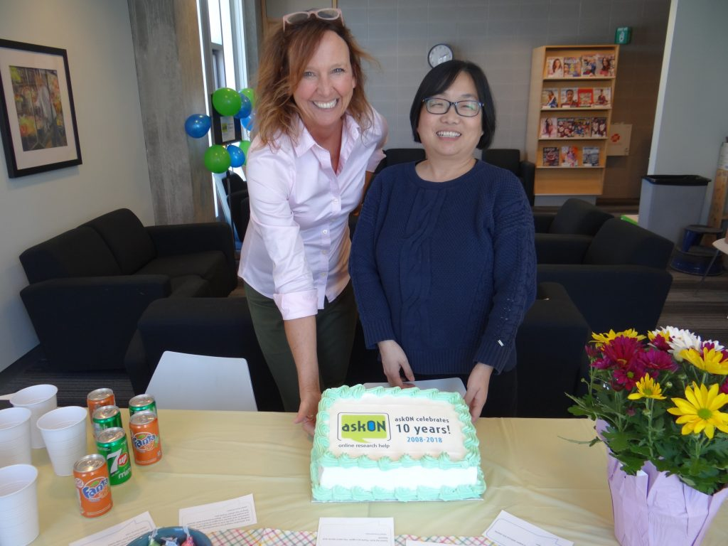 Portrait of two librarians from Durham College with an askON celebratory cake.