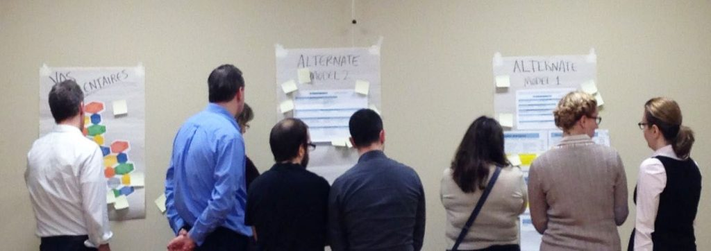 A group of people, their back to the camera, are observing sheets of paper and sticky notes taped to a wall.