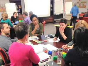 People engaged in discussion around a table, on which there are colourful play blocks, sheets of paper and sticky notes. Another table is seen in the background, as well as a person standing reading a flip chart (illegible text).