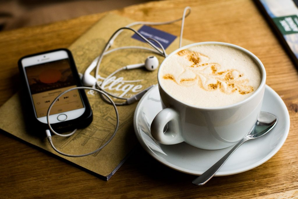 Photo of a full coffee cup and cell phone with headphones attached.