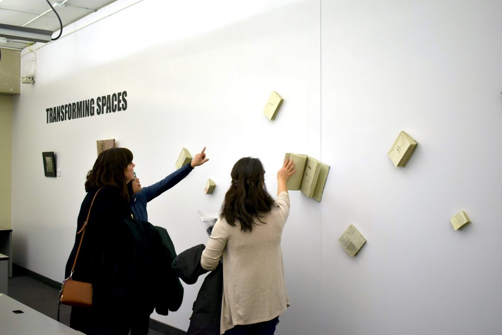 Three women, their back to the camera, are seen interacting with an art installation involving books attached to a wall. One is flipping through the pages of one of the attached books. The words Transforming Spaces are printed on the wall.