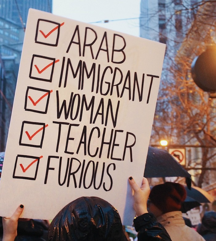 A woman is holding a poster with words arab, woman, immigrant, teacher, furious checked off.