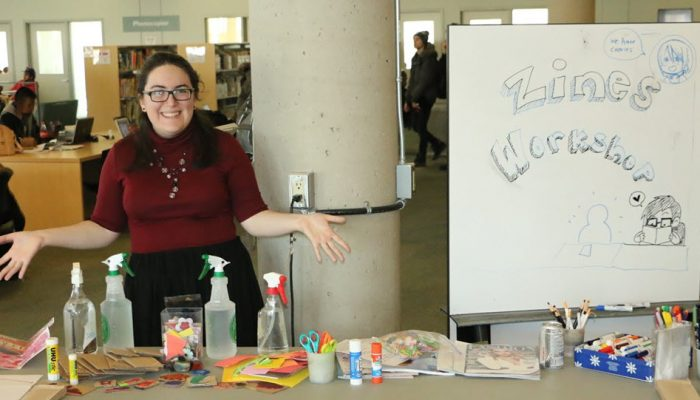 Woman Standing At Table With Craft Supplies For Zine Workshop