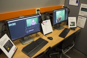 Two desktop computers on a bench. The image of a person in front of a green screen is visible on one of the computer screens.