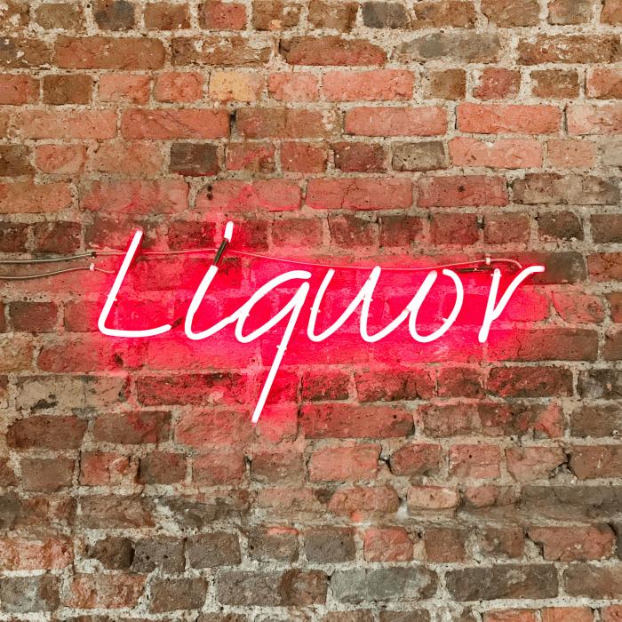 Pink neon sign on brick wall says liquor