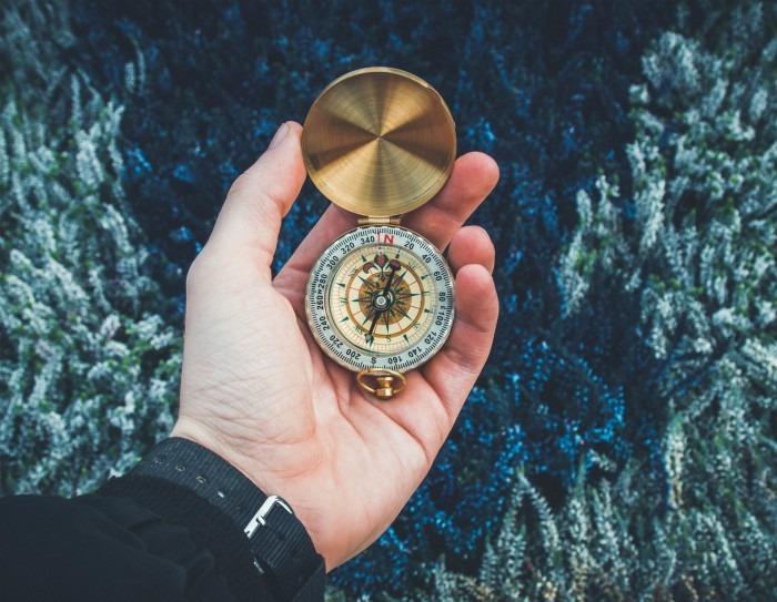 A Man's Hand Holding A Gold Compass