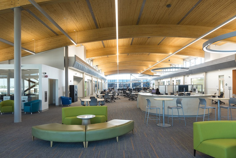 Interior view of the library space at Algonquin College. Low sofas and bar tables and stools are seen in the foreground, with a reference desk.