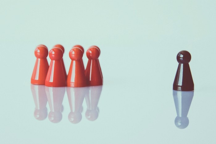 Image of a group of red game pieces set a part from a single black game piece on a turquoise background