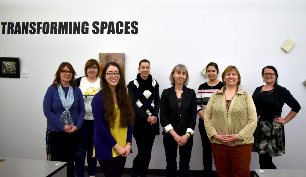 The image represents a group of 8 women standing in front of the exhibition wall. The words Transforming Spaces are printed on the wall. Art can be partly seen behind the group.