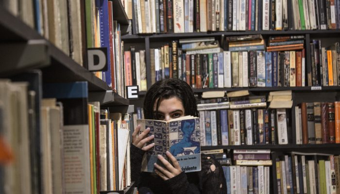 Photo Of A Woman Surrounded By Books, Covering Her Face With A Copy Of 1984.
