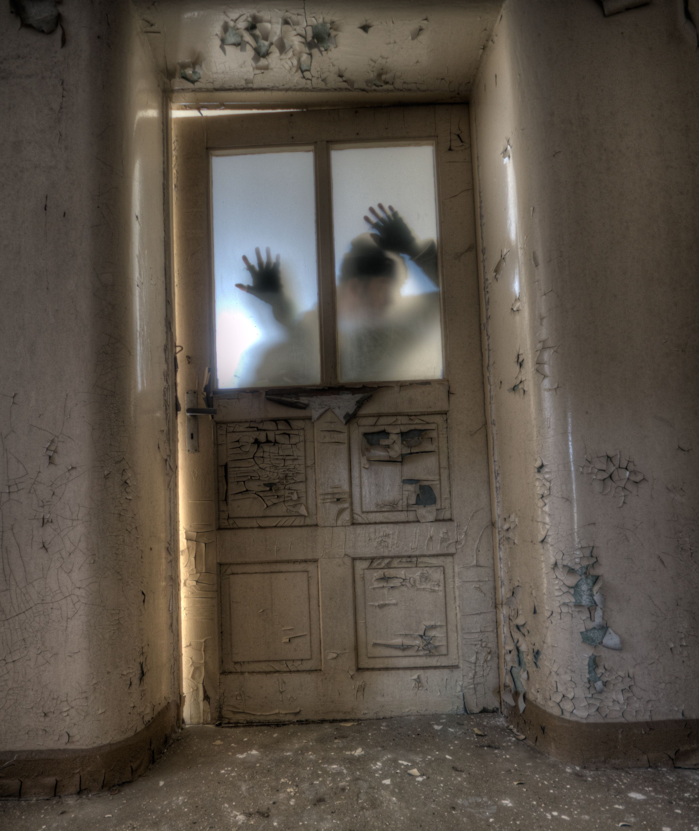 A hand placed against a door