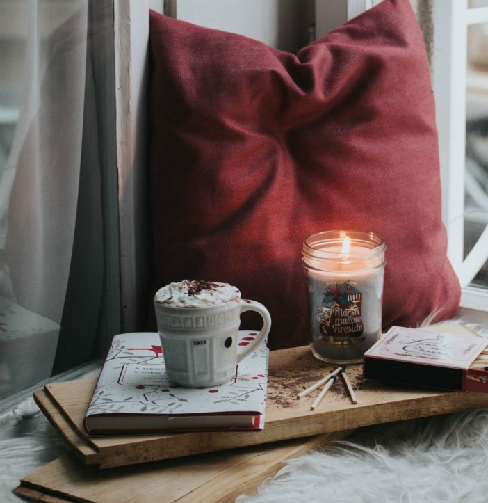 A photo of a pillow, with a candle and a cup of chocolate