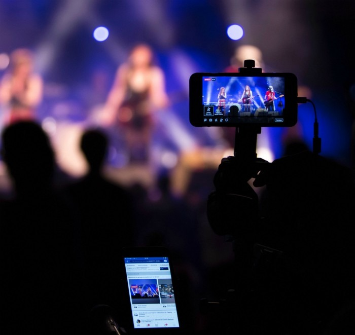 A Picture Of A Cell Phone Streaming A Live Concert