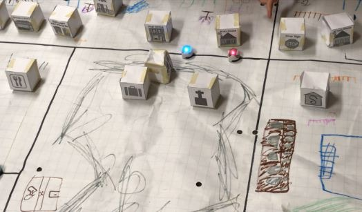 Cardboard buildings on top of a paper map with roads and movement recorded in pencil and crayons.