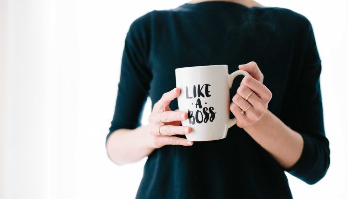 Woman Standing With A Mug That Reads Like A Boss