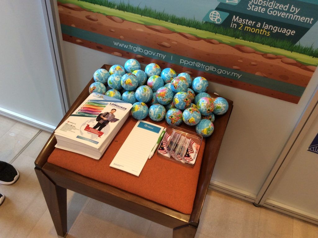A table on which sit pamphlets and small globes