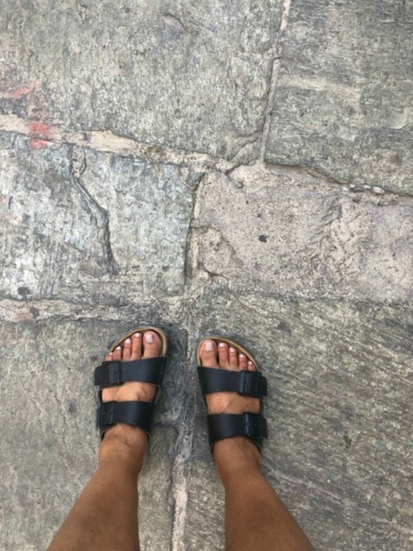 A pair of feet in sandals on a concrete sidewalk