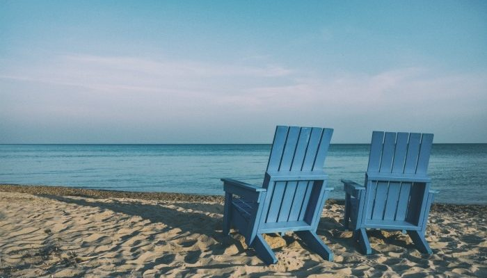 Two Blue Adirondack Chairs On A Beach Facing The Ocean