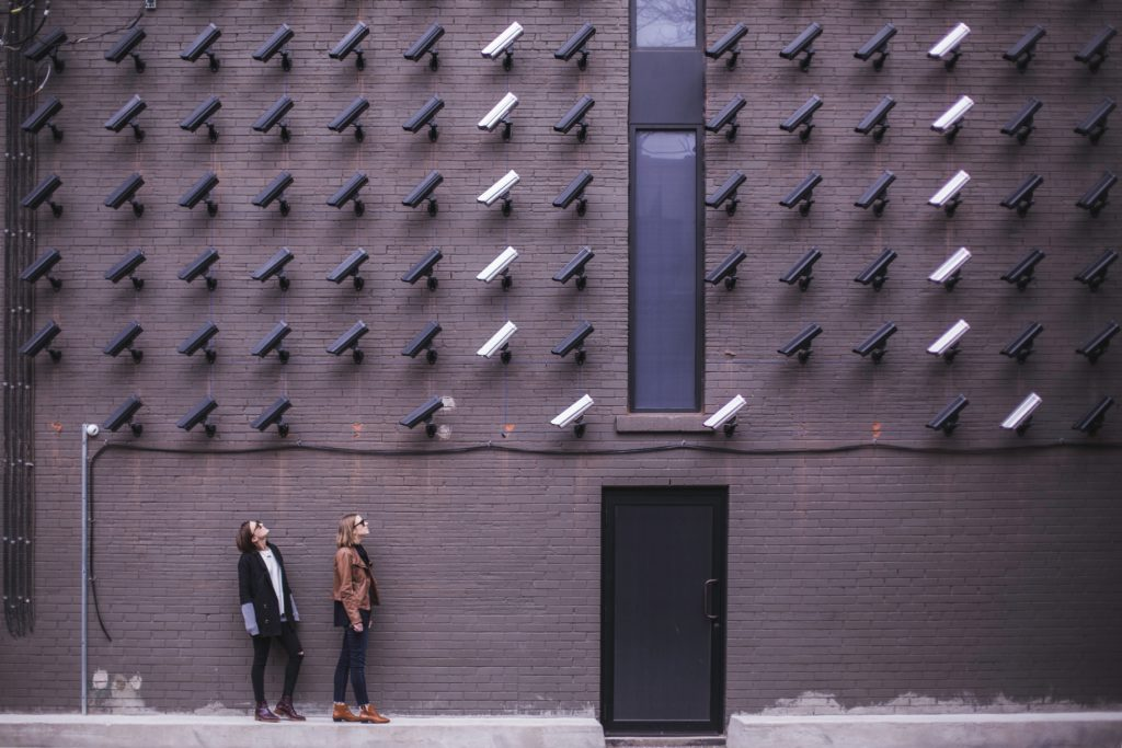 Two women underneath a wall of video cameras