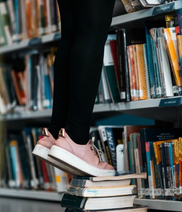 Girl Standing On Pile Of Books