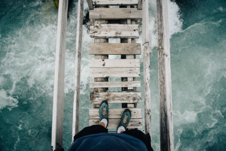 A person is standing on a wooden bridge looking down at rushing water.