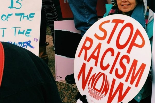 A Woman Sitting Holding A Sign That Says Stop Racism Now