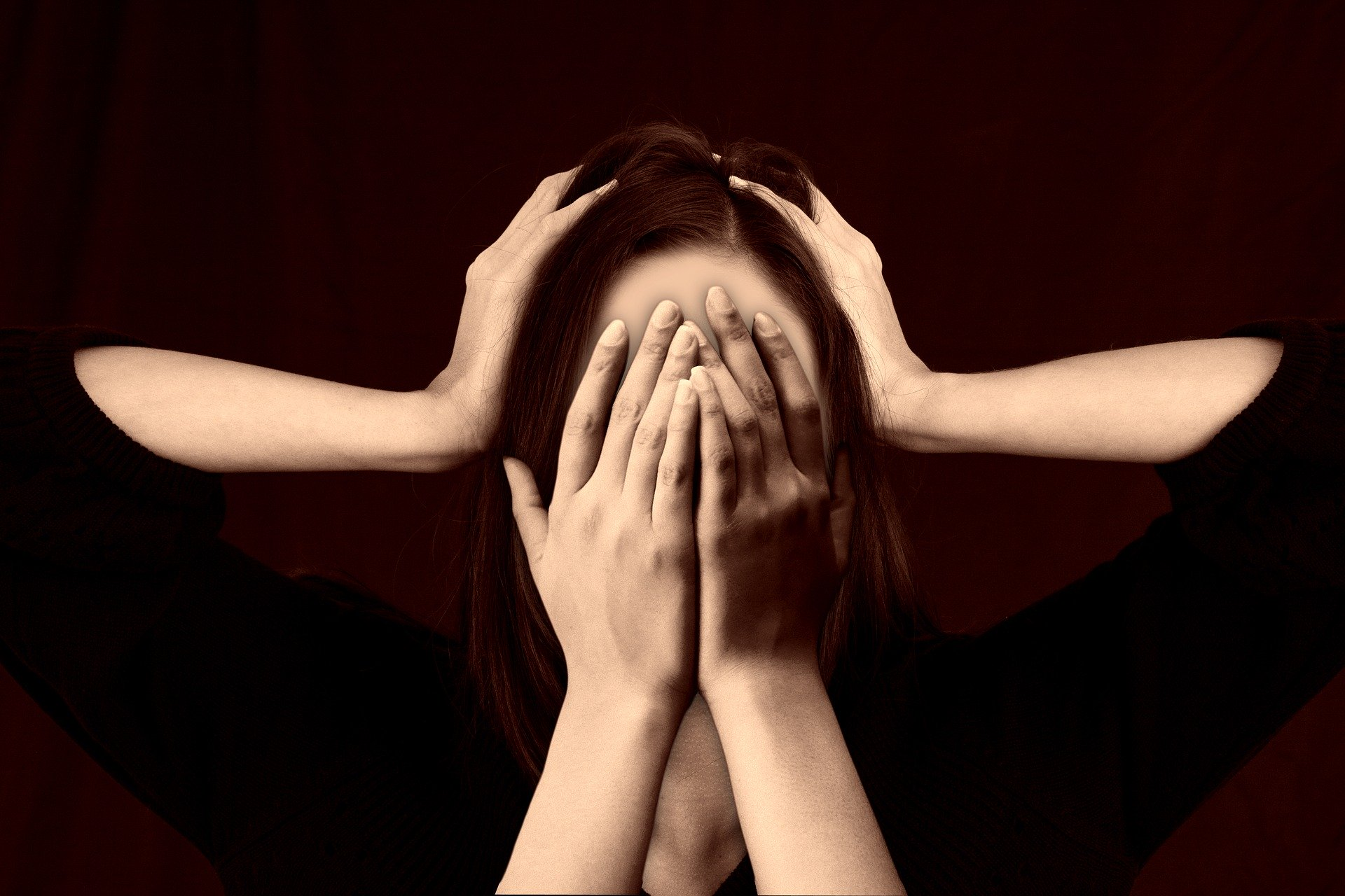 Woman covering ears and other hands covering her face.