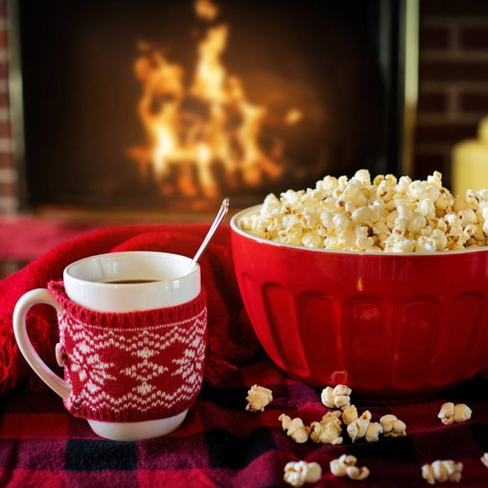 Hot Drink And Popcorn On A Table, In Front Of A Fire