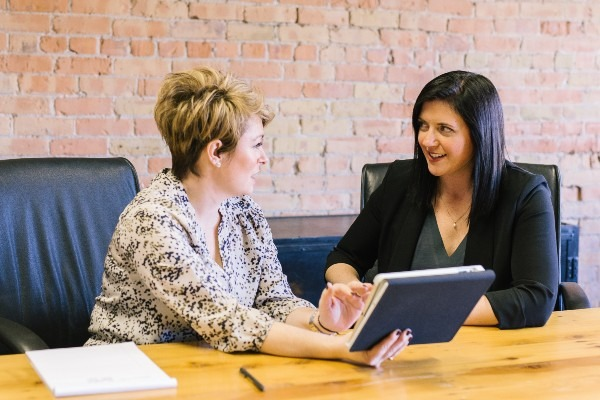 Two women sit at a table conducting an interview exercise