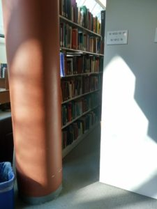 Sunlight falling on the end of a shelf and highlighting the crowded materials it contains