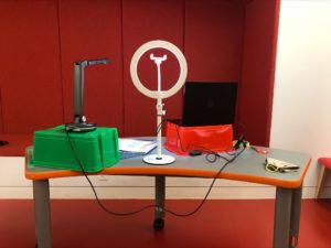A streaming setup for digital library programming including a ring light, laptop and camera for easy display of books.