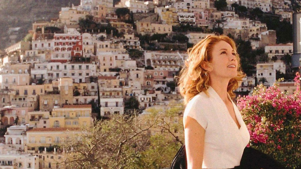 A woman stands in front of a coastal Mediterranean city in the sun