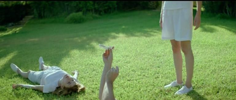 Children lie on a manicured lawn in the sun in the film Kynodontas