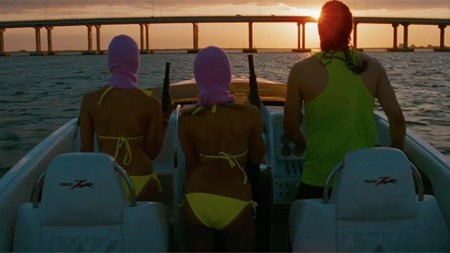 Two of the four female leads of Spring breakers boat into the sunset with James Franco, bearing assault rifles