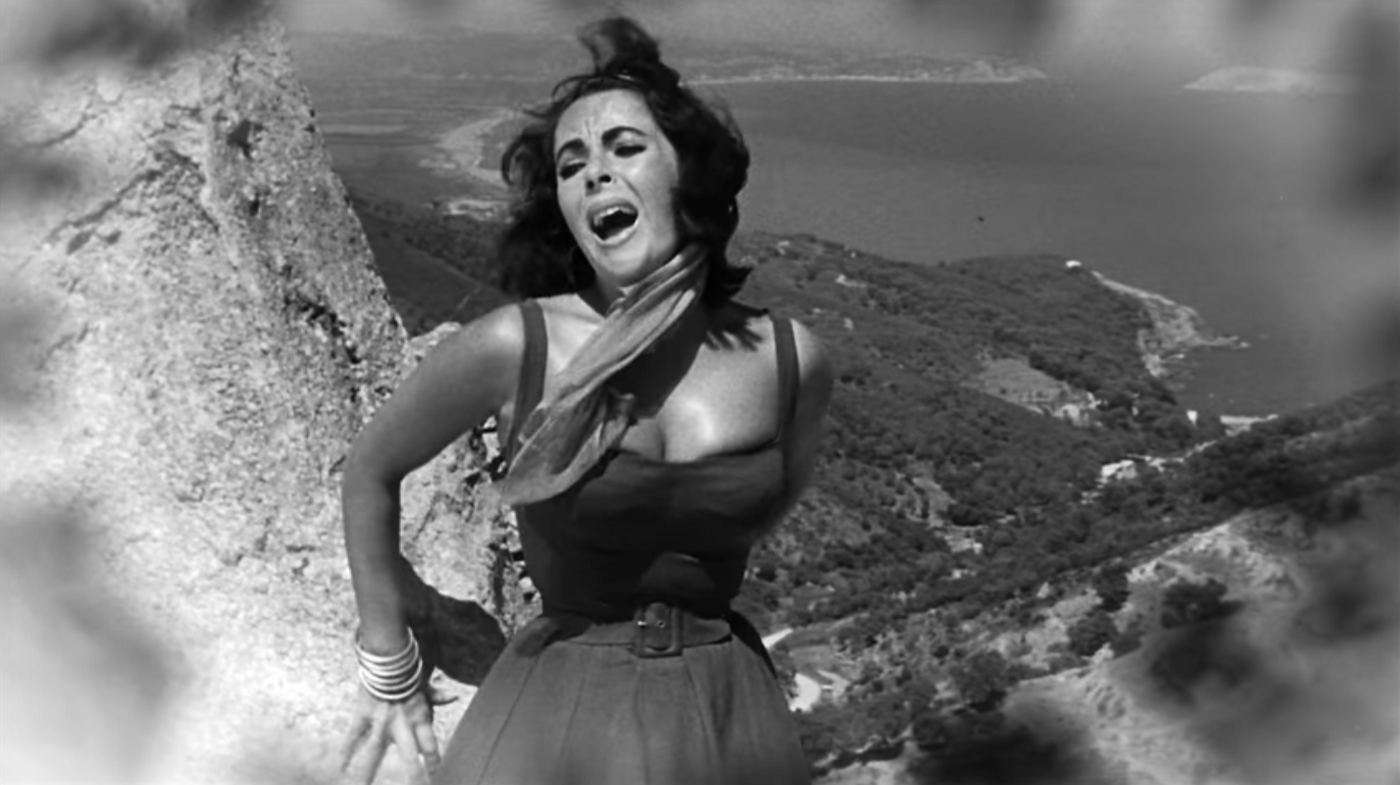 Elizabeth Taylor leans against a rock in panic in the film Suddenly Last Summer