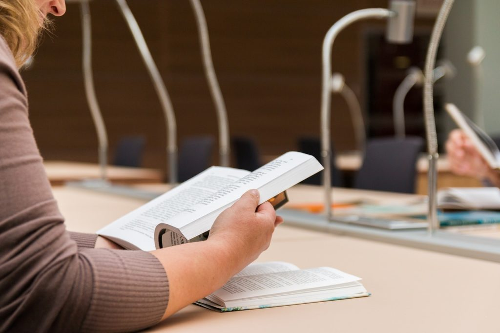 A library patron readying a book in the library